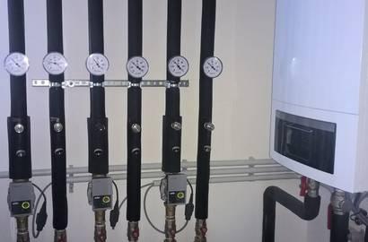 Rozdělovač/sběrač topného systému s čerpadlovými sestavami.